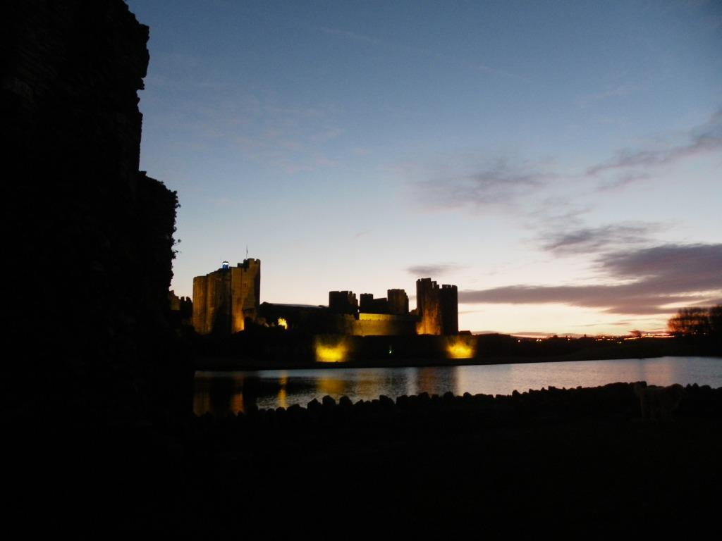 Caerphilly Castle floodlit- castle and moat silhouetted against a clear evening sky at night