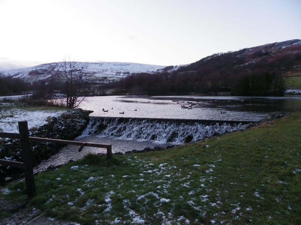 Dare Valley Country Park in Winter lake and weir with backdrop of snow covered mountains