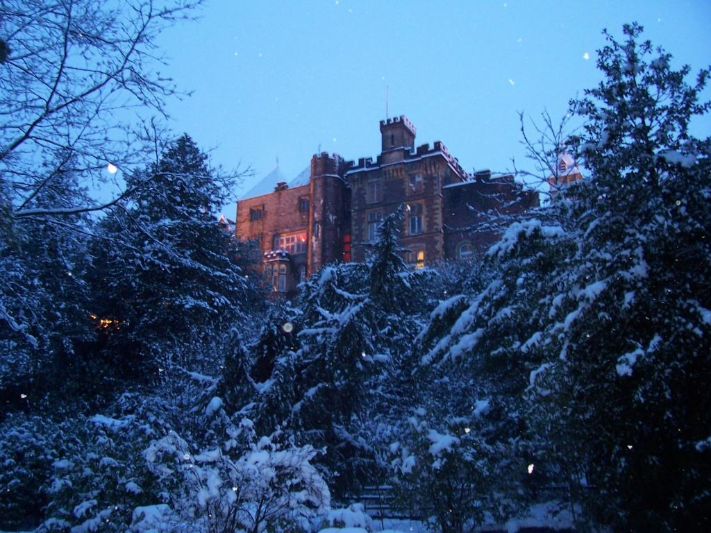 Dog Friendly Hotel Wales, rear view of Craig y Nos Castle in snow in evening