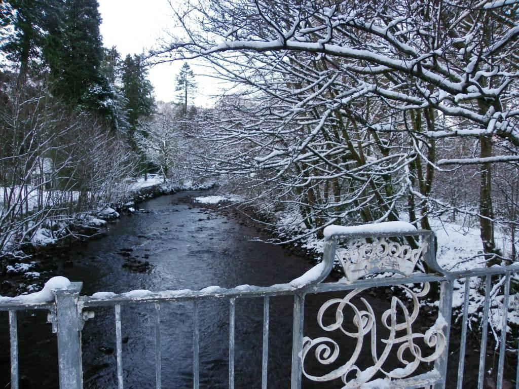 Dog Friendly Hotel Swansea Wales Craig y Nos Country Park Adelina Patti Logo on footbridge over River Tawe in Winter Snow